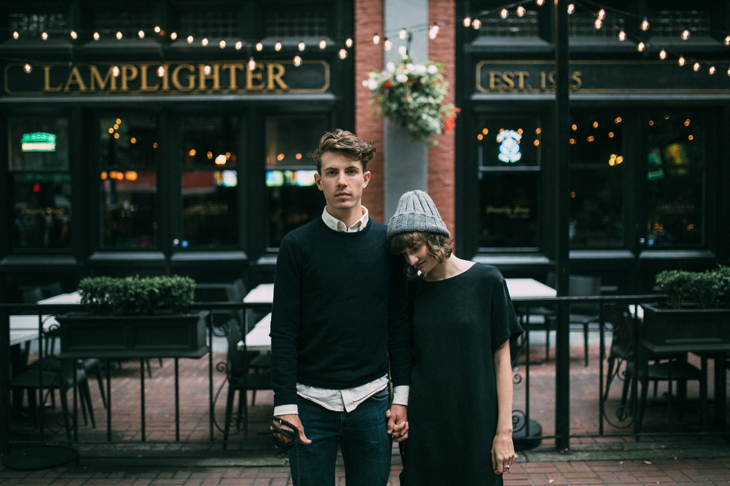 Trendy couple standing in front of the Lamplighter in Gas Town with dog