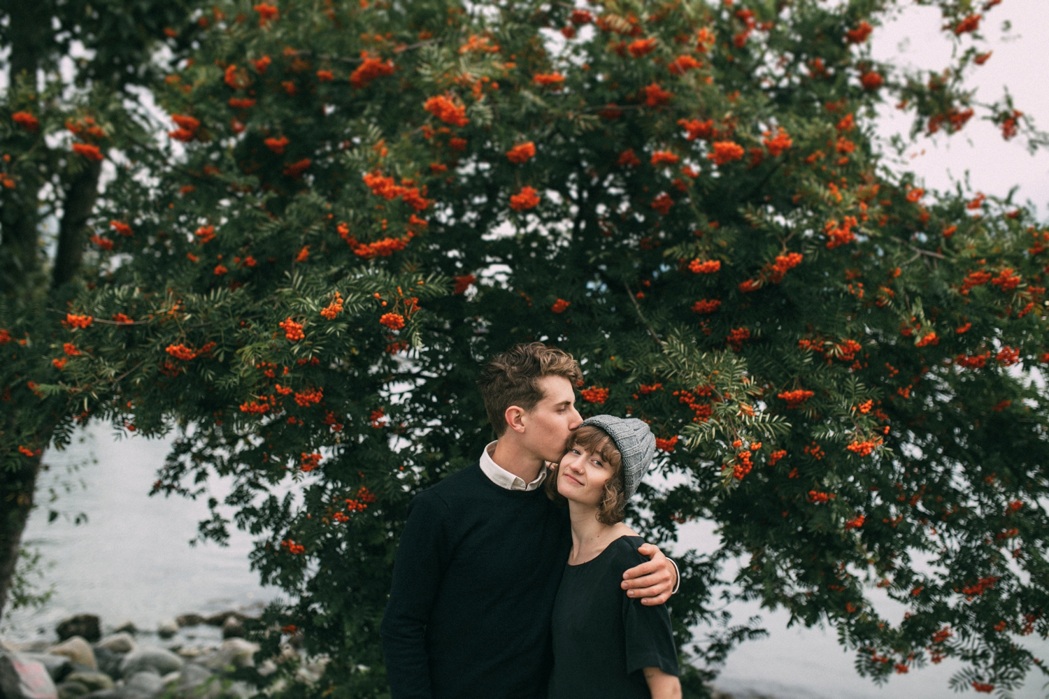 Couple In Love Stand In Front Of Red Berry Bush