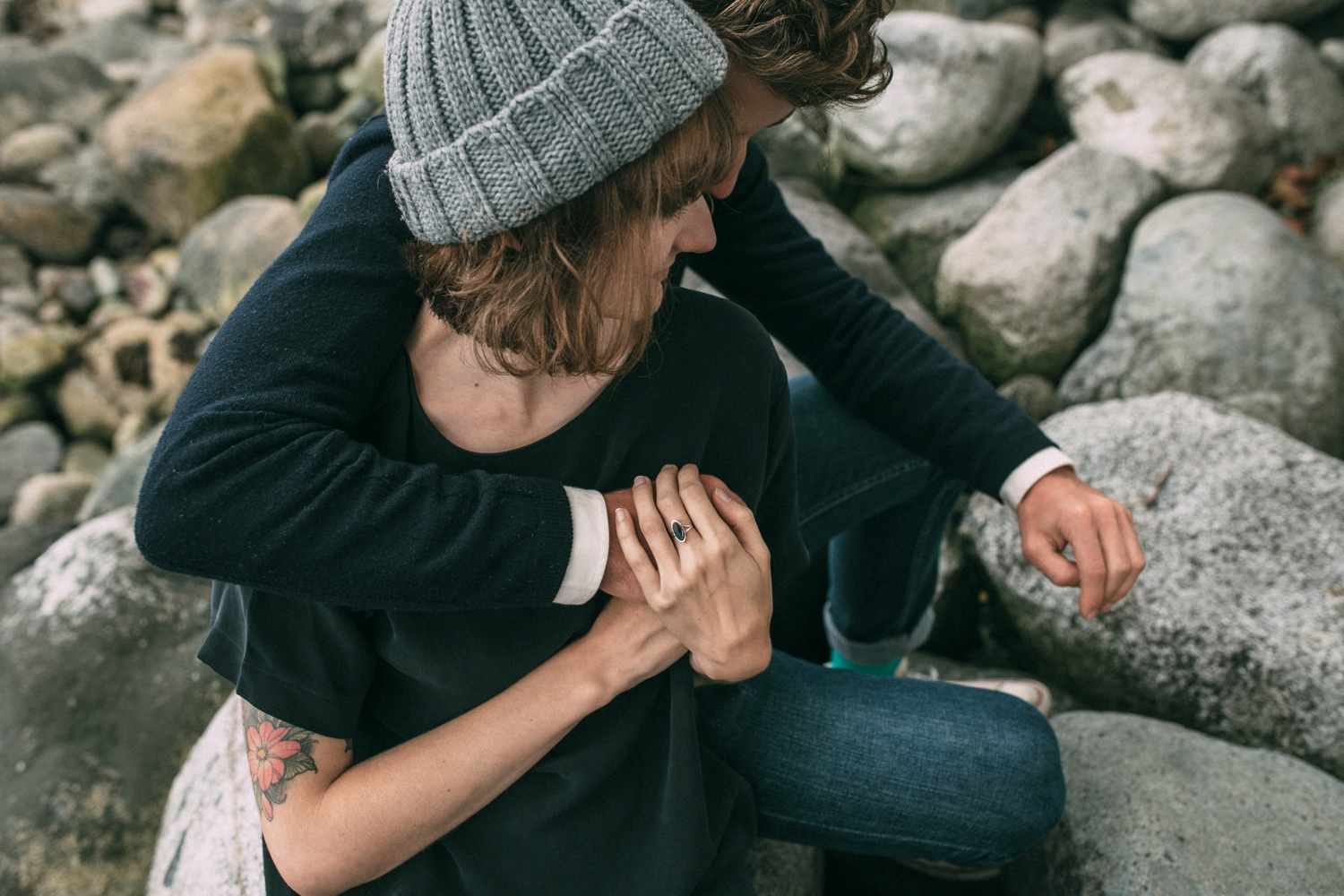 Engagement photo shoot of hipster couple with tattoos sitting together on the rocks on the beach in Vancouver