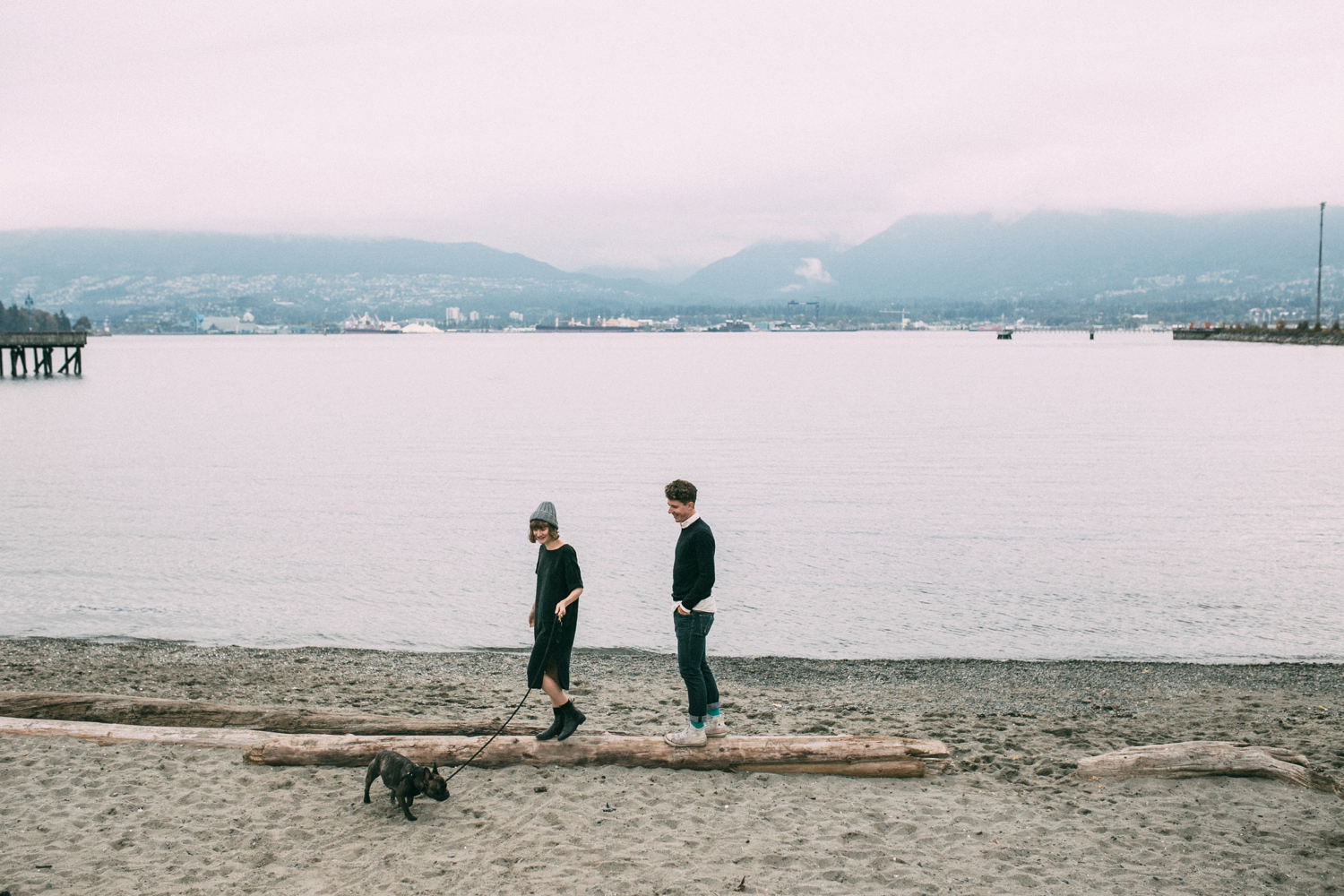 Epic image of couple walking their dog on the beach at sunset in Vancouver, BC
