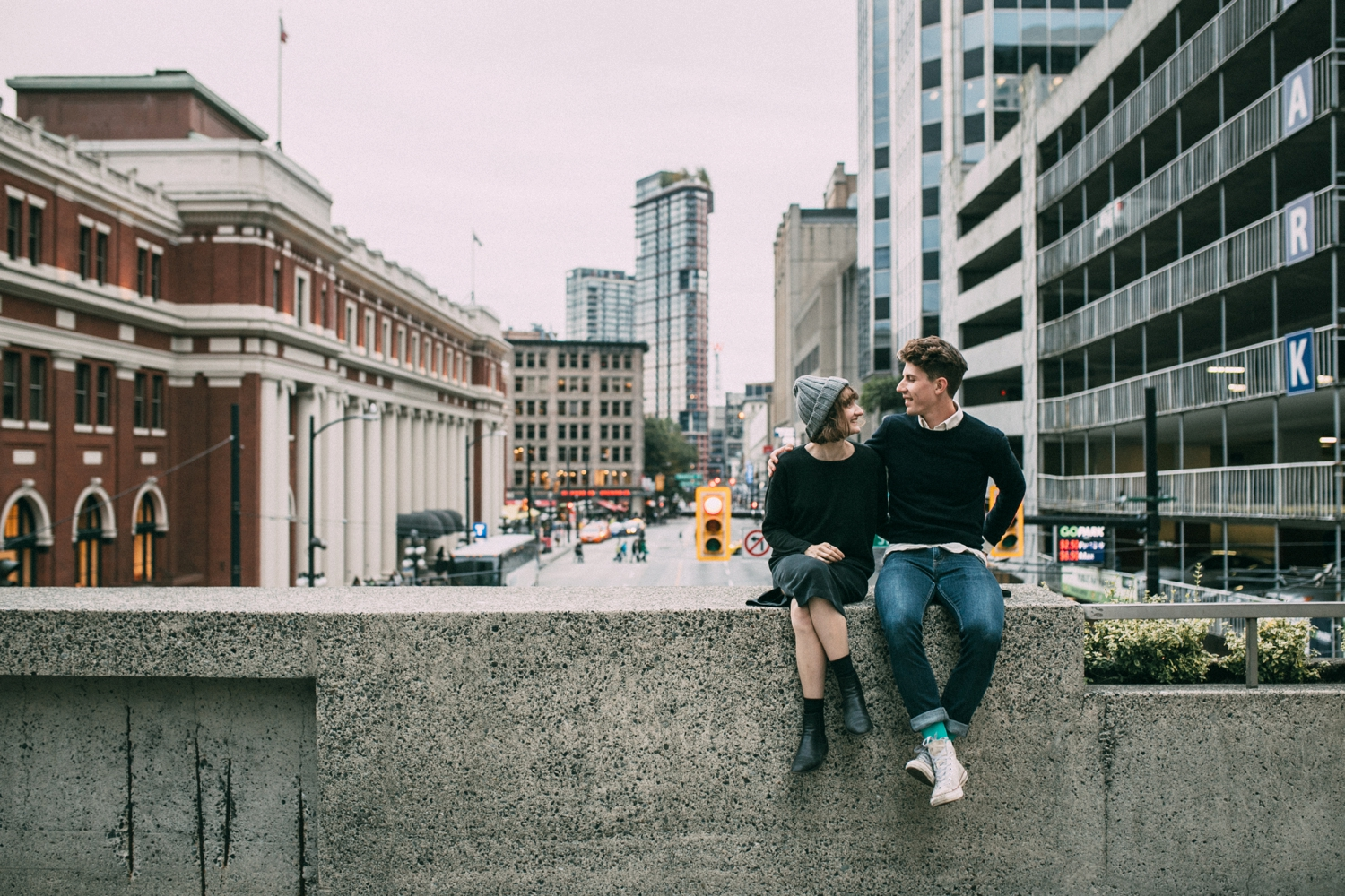 Alternative Couple Sitting on Wall Talking Downtown Vancouver