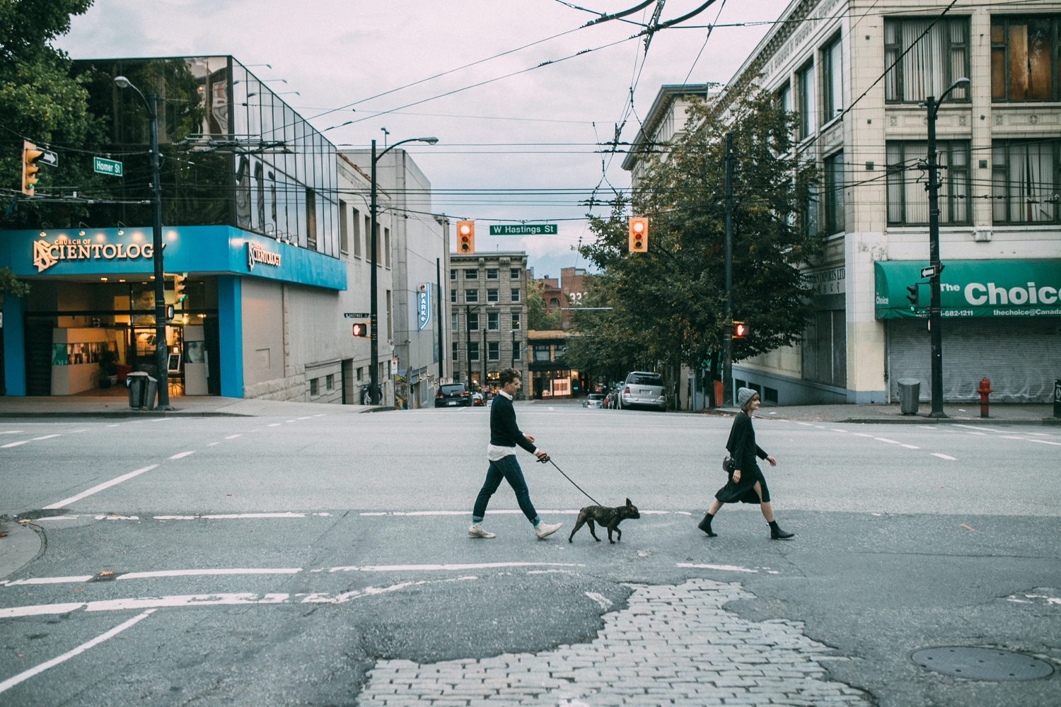 Photojournalist Wedding Photographer based in Vancouver Canada captures couple walking on the city streets with their dog