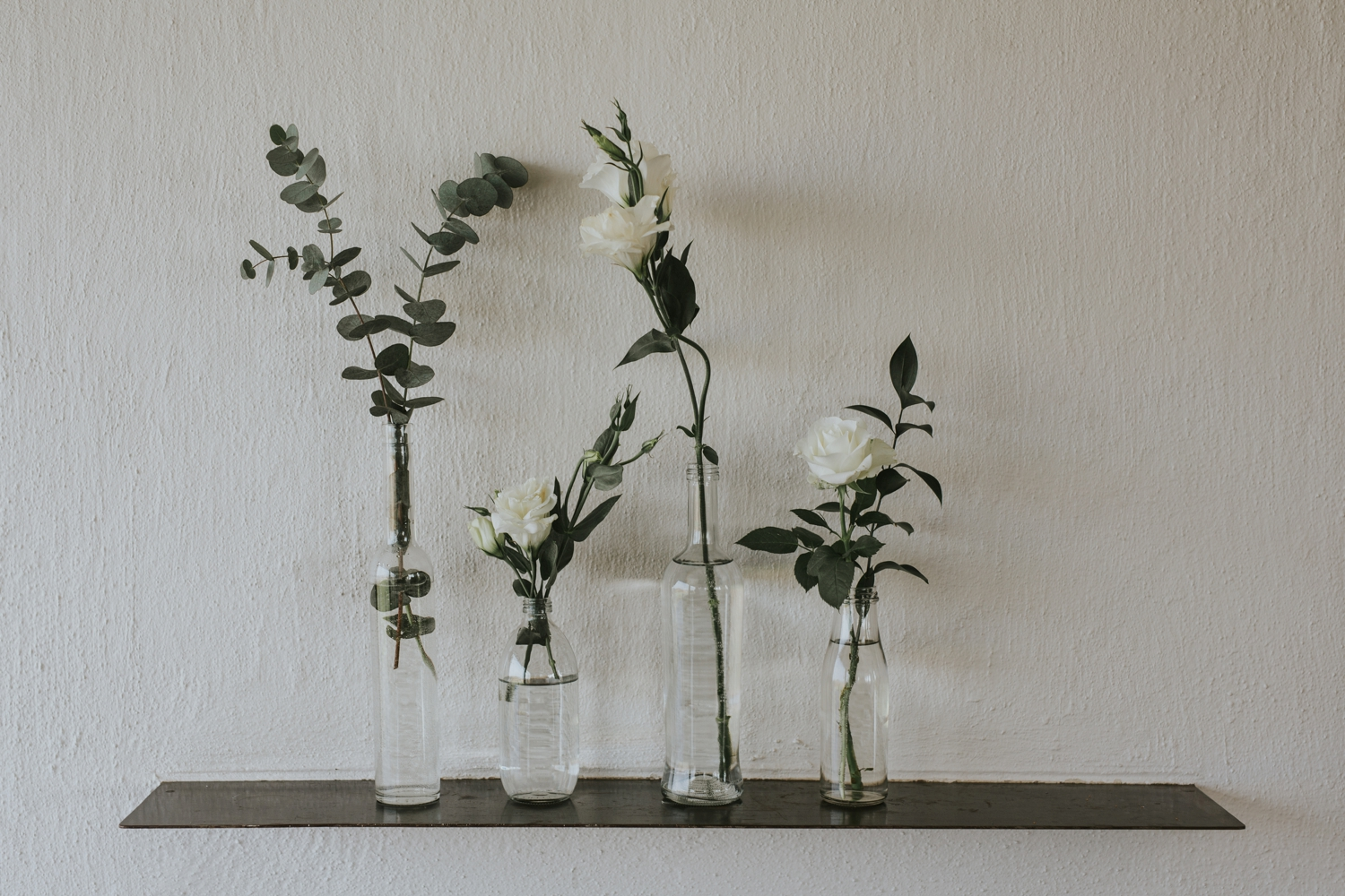 Simple wedding flowers, simple glass bottles with springs of eucalyptus and white roses at classic Vancouver wedding.