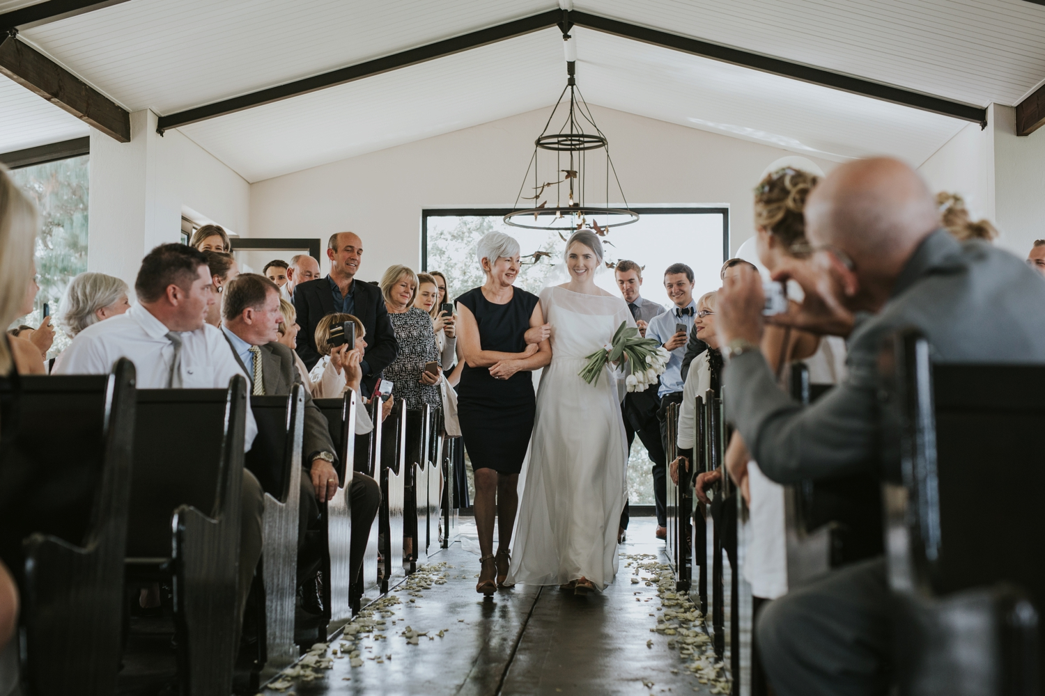 Candid and beautiful wedding moment of mother walking her daughter, the bride, down the aisle at Netherwood Wedding Venue in the Natal Midlands