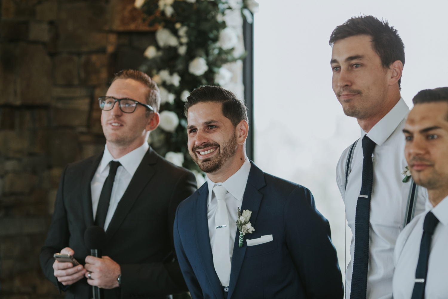 Happy and emotional photo of groom laughing and crying as he watches bride walk down the aisle at Vancouver wedding ceremony at Cecil Green Park House