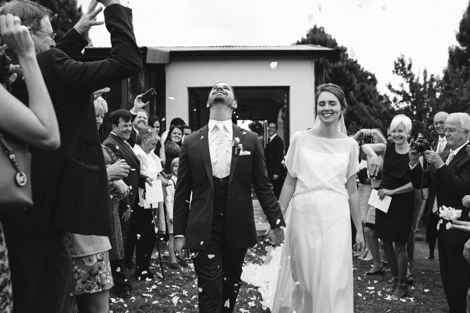 Bride and groom walk down aisle during confetti throw of white roses in farm wedding in Vancouver