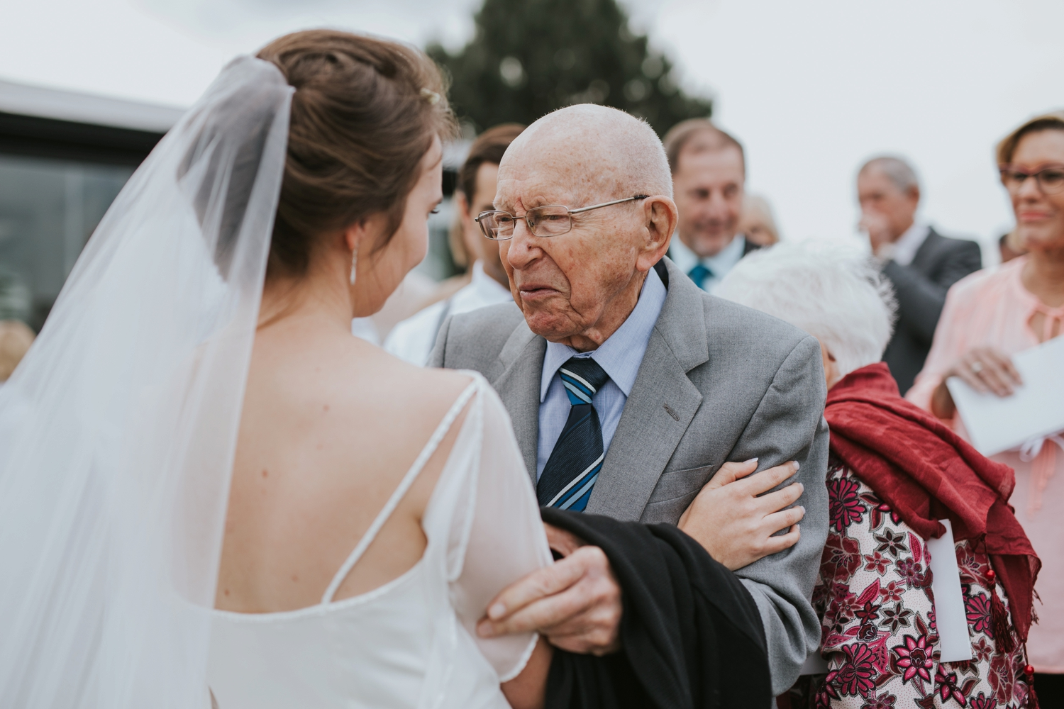 Candid moment of grandfather congratulating bride on her marriage at Cecil Green Park House