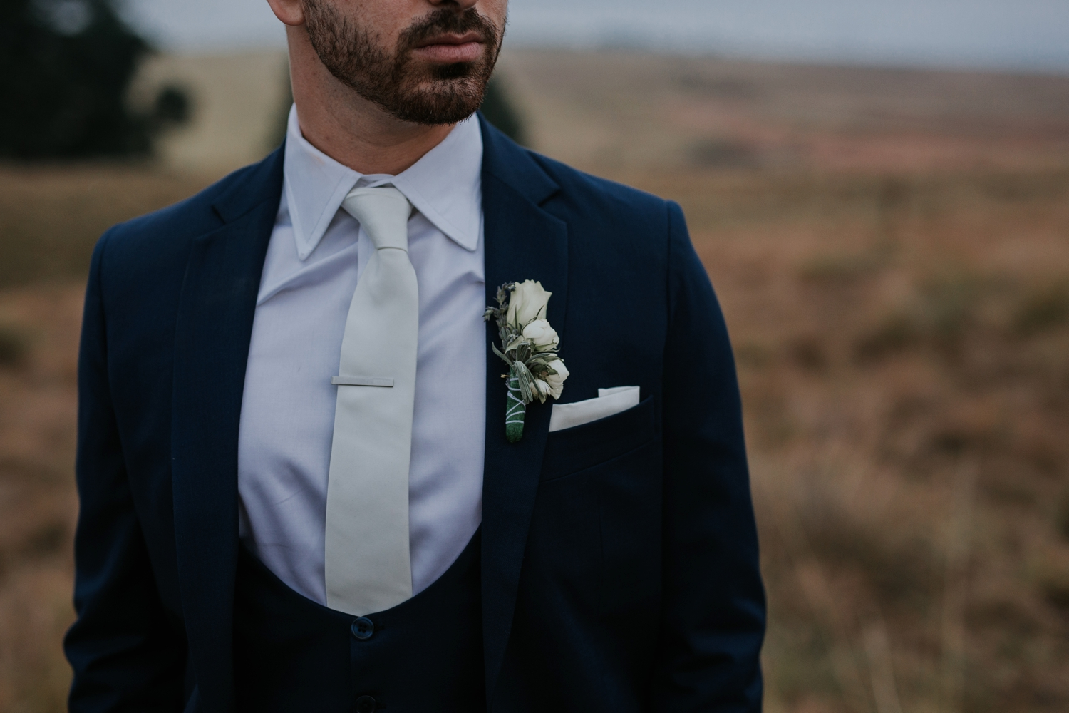 Groom wars simple white rose lapel and trendy suit in wedding portrait photography session by candid Vancouver wedding photographer