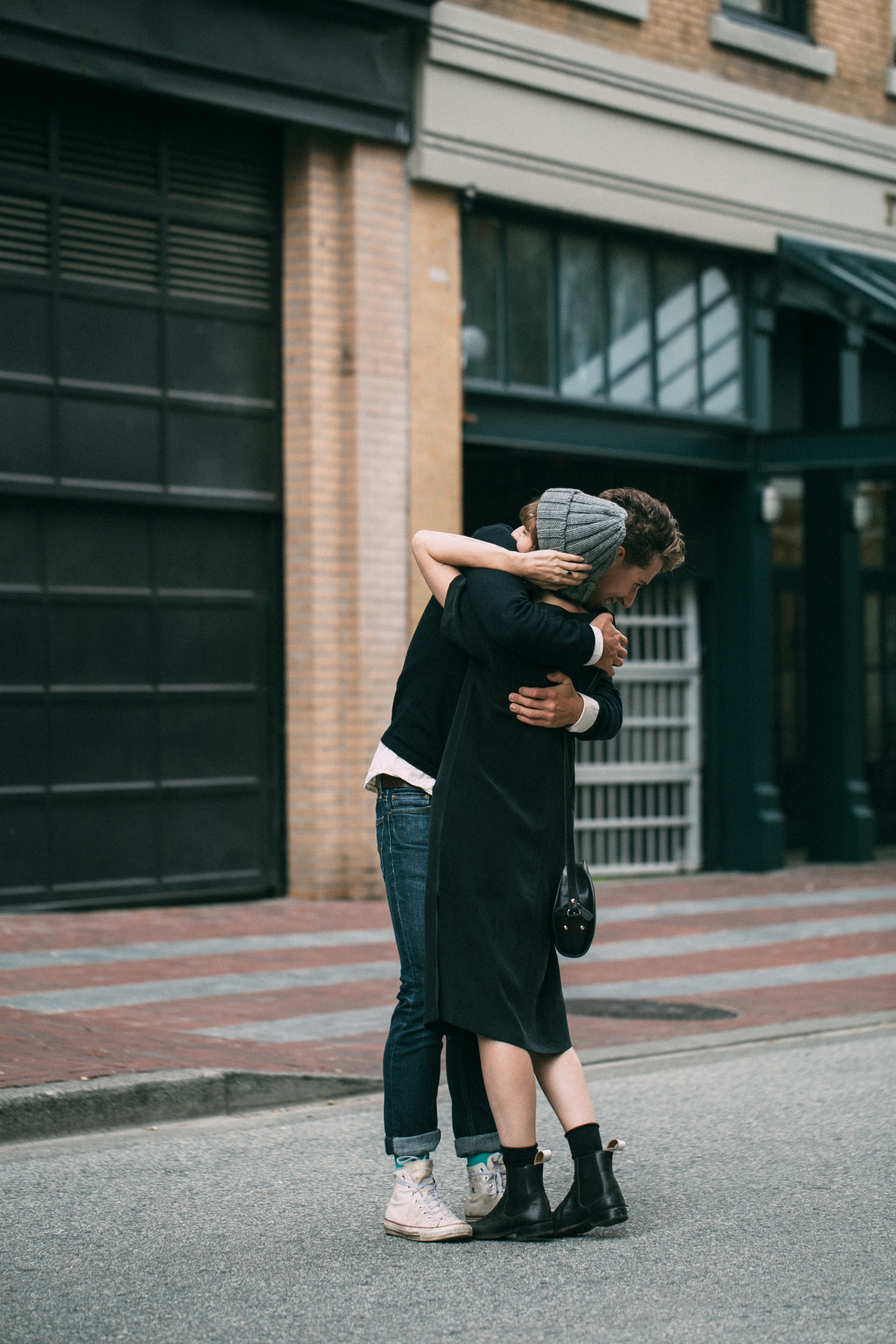 Candid moment of engaged, alternative couple hugging each other during engagement photo session in Gas Town, Vancouver.