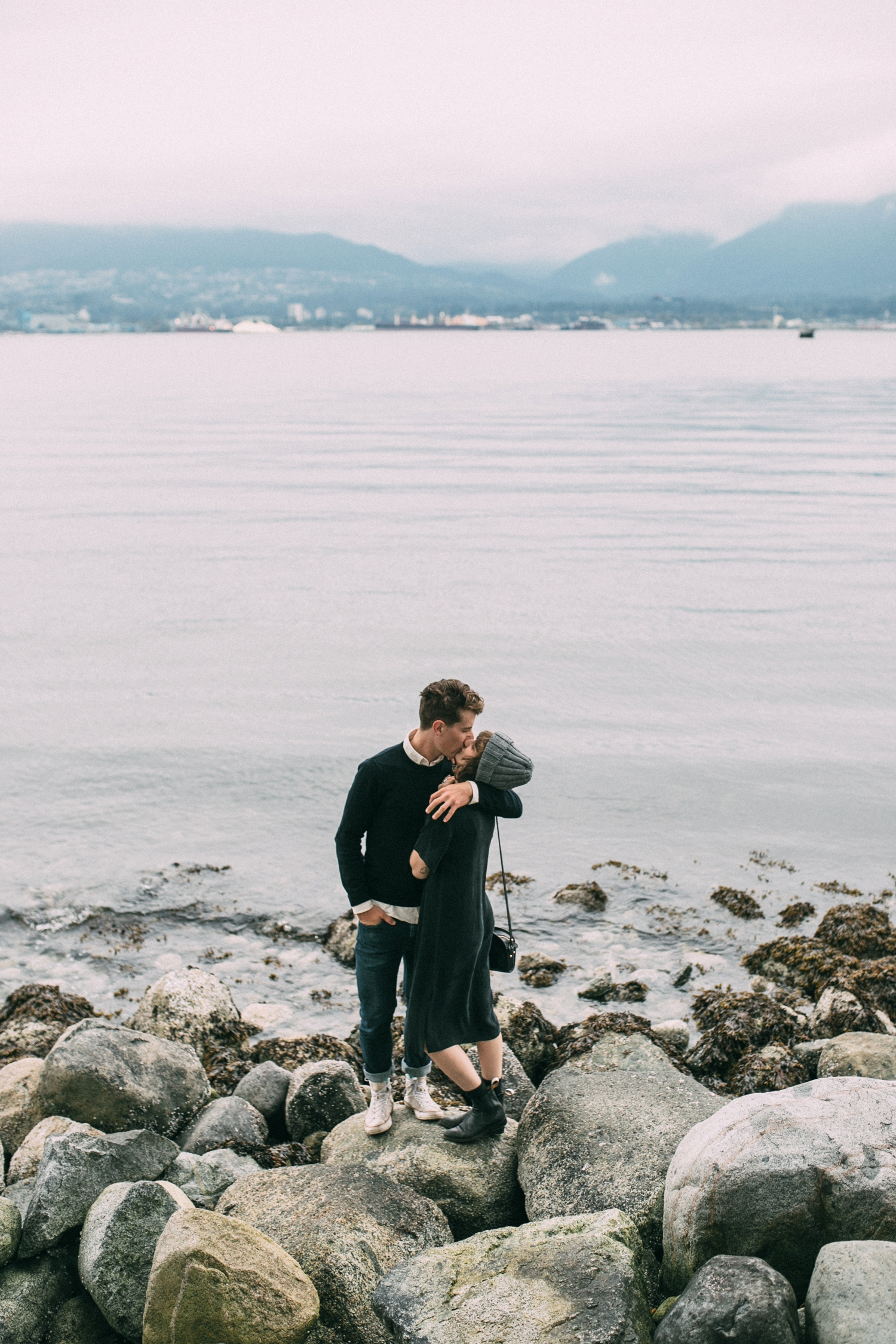 Natural and Authentic Moment of couple kissing each other on the sea rocks near Gas Town in Vancouver