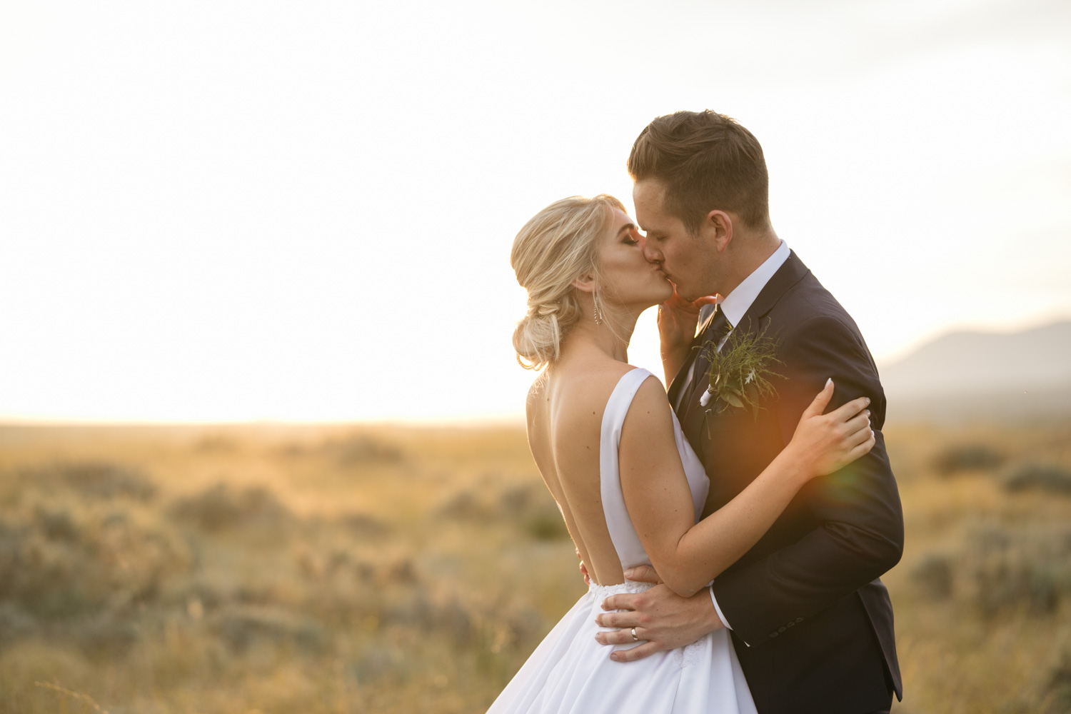 Bride and Groom Kiss in Golden Field At Top Of Vancouver Mountain in Summer