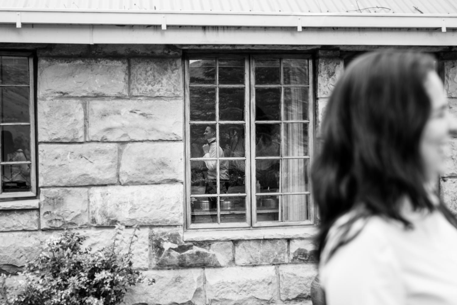 Interesting Alternative Wedding Photograph Of Reflection Of Groom Putting On Tie In WIndow