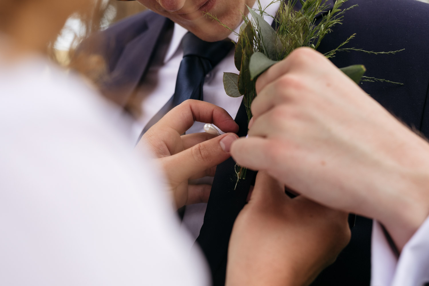 Groomsmen Putting On Groom's Trending Eucalyptus Leaf And Fynbos Lapel