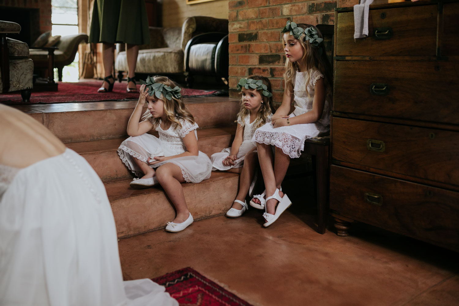 Flower Girls Wearing Eucalyptus Leaf Flower Crowns And White Dresses Sit On Stairs Watching Bride