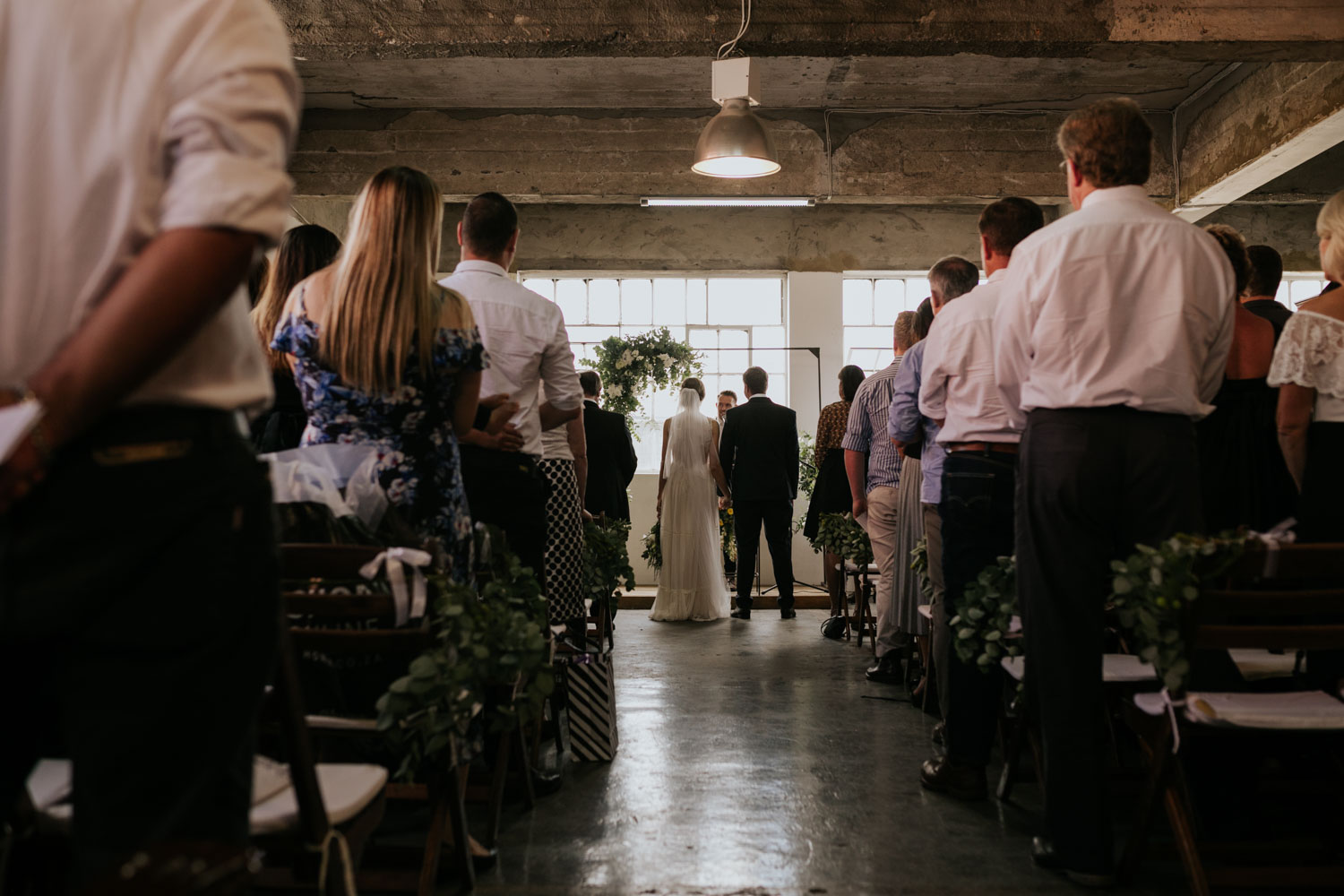Bride And Groom Stand Hand In Hand in Vancouver Warehouse Wedding Ceremony