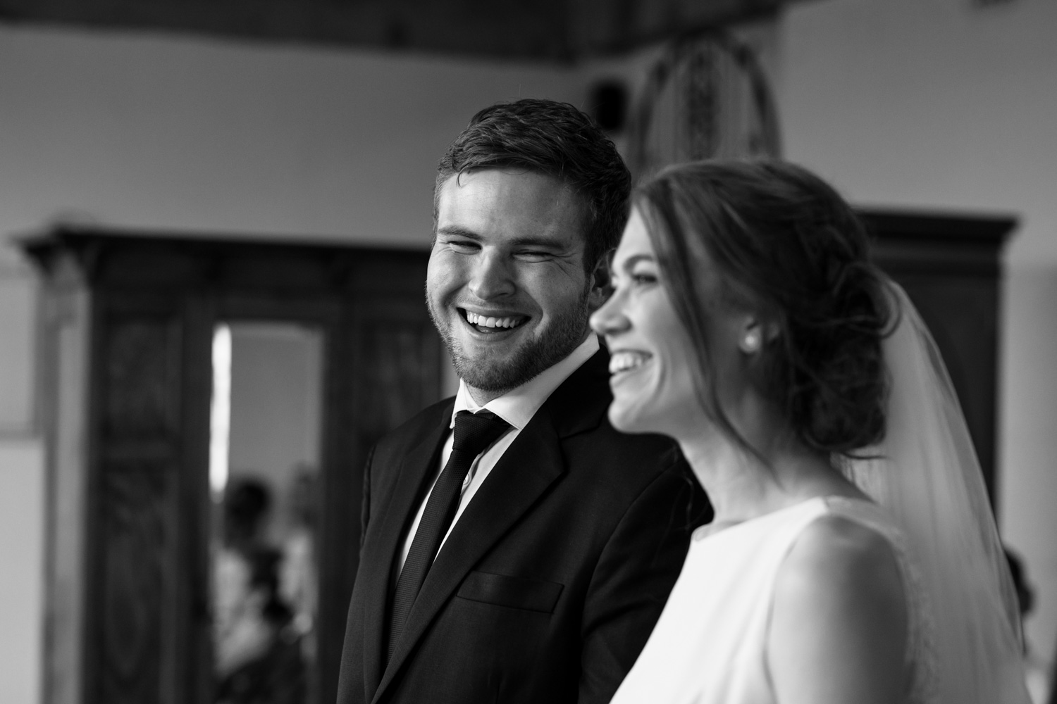 Groom Wearing Class Black Suit Smiles At Bride In Vancouver Wedding Ceremony