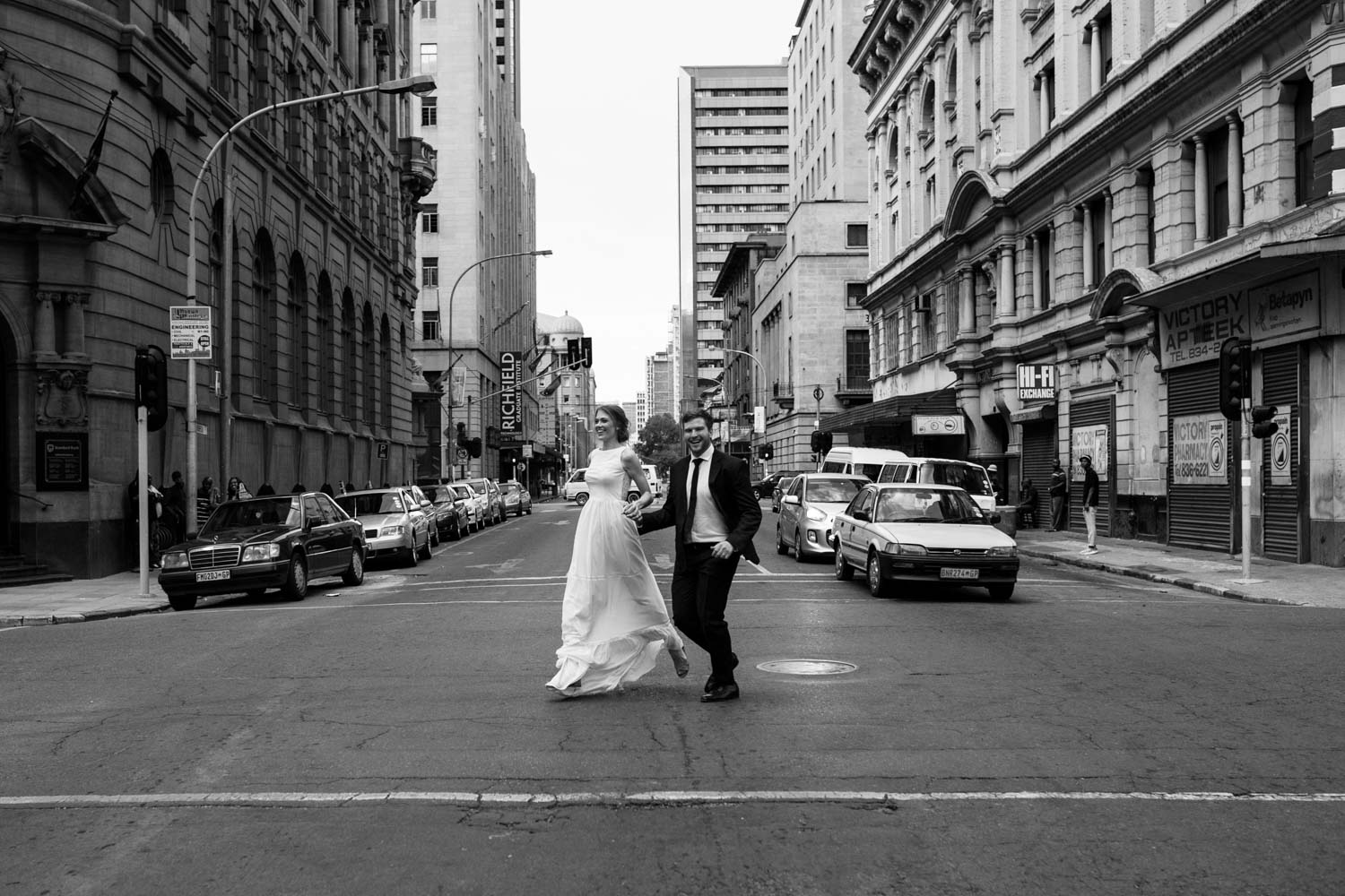 Bride And Groom Run Down Street In Victoria, Vancouver Island
