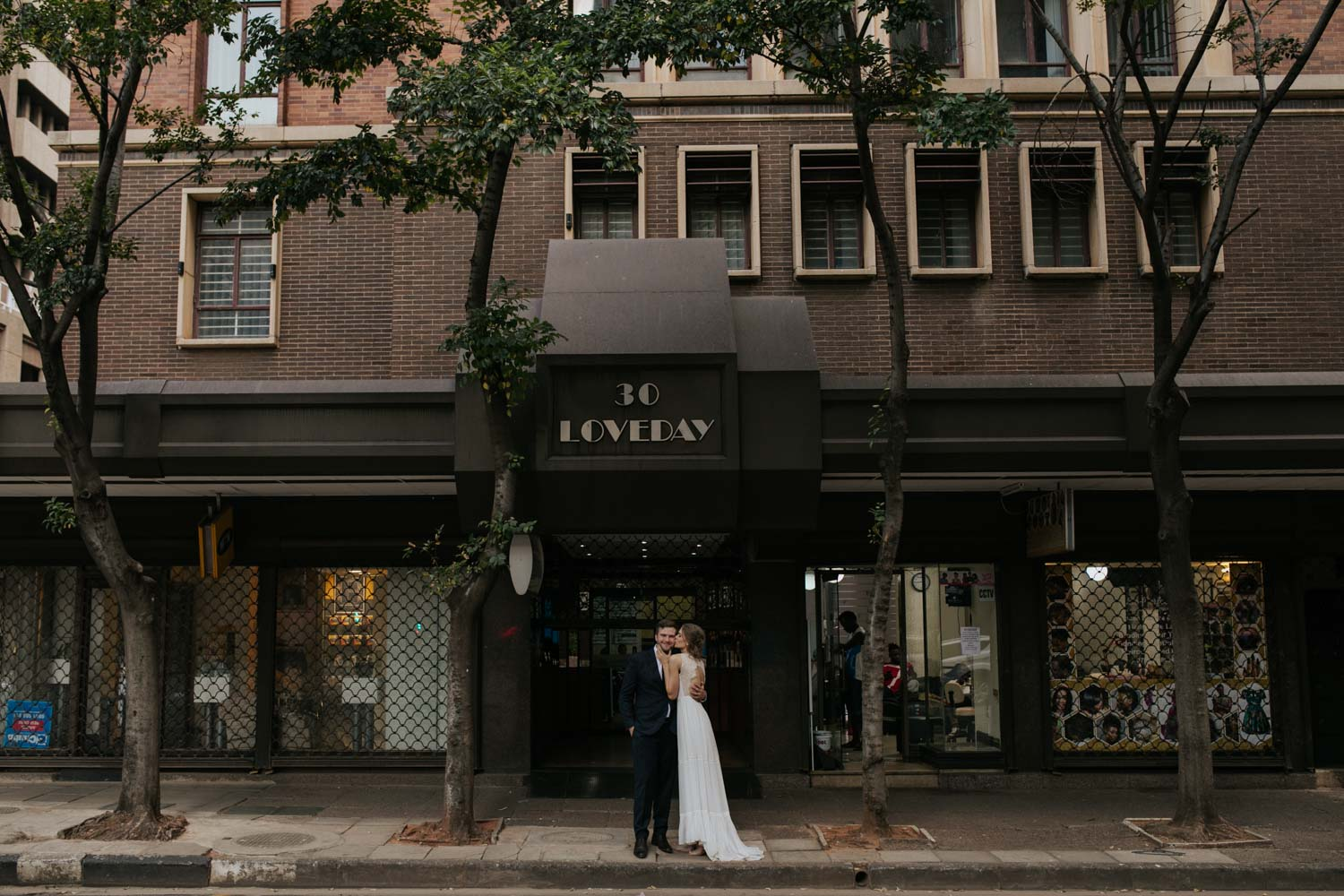 Bride Kisses Grooms' Cheek In Front Of Epic Old Vancouver Heritage Building
