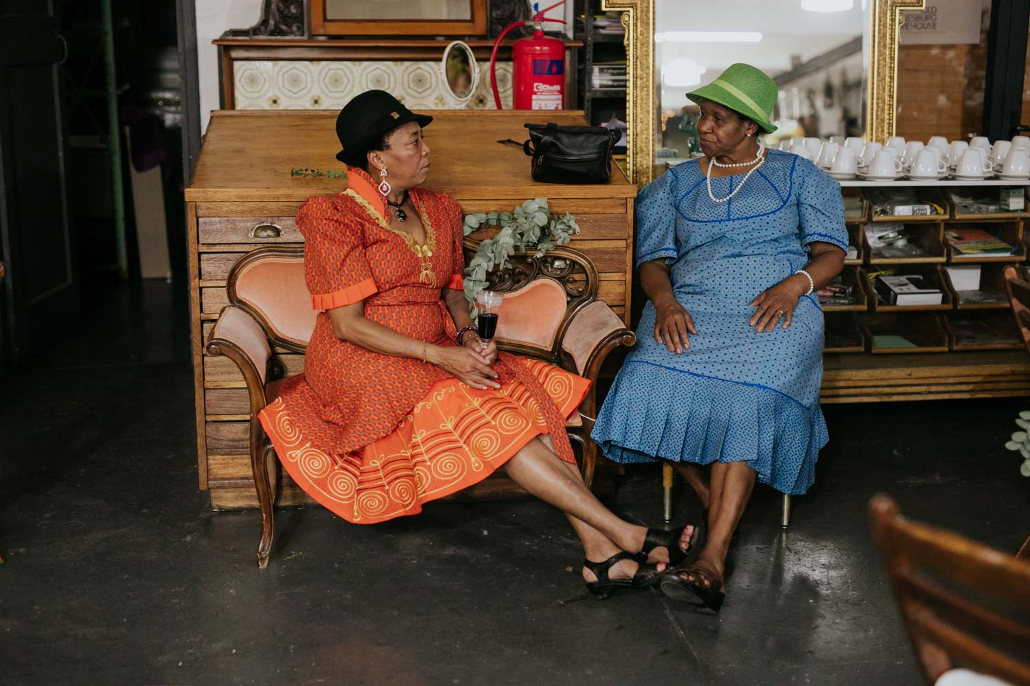 Two African Mamas Drink Tea During Wedding Reception