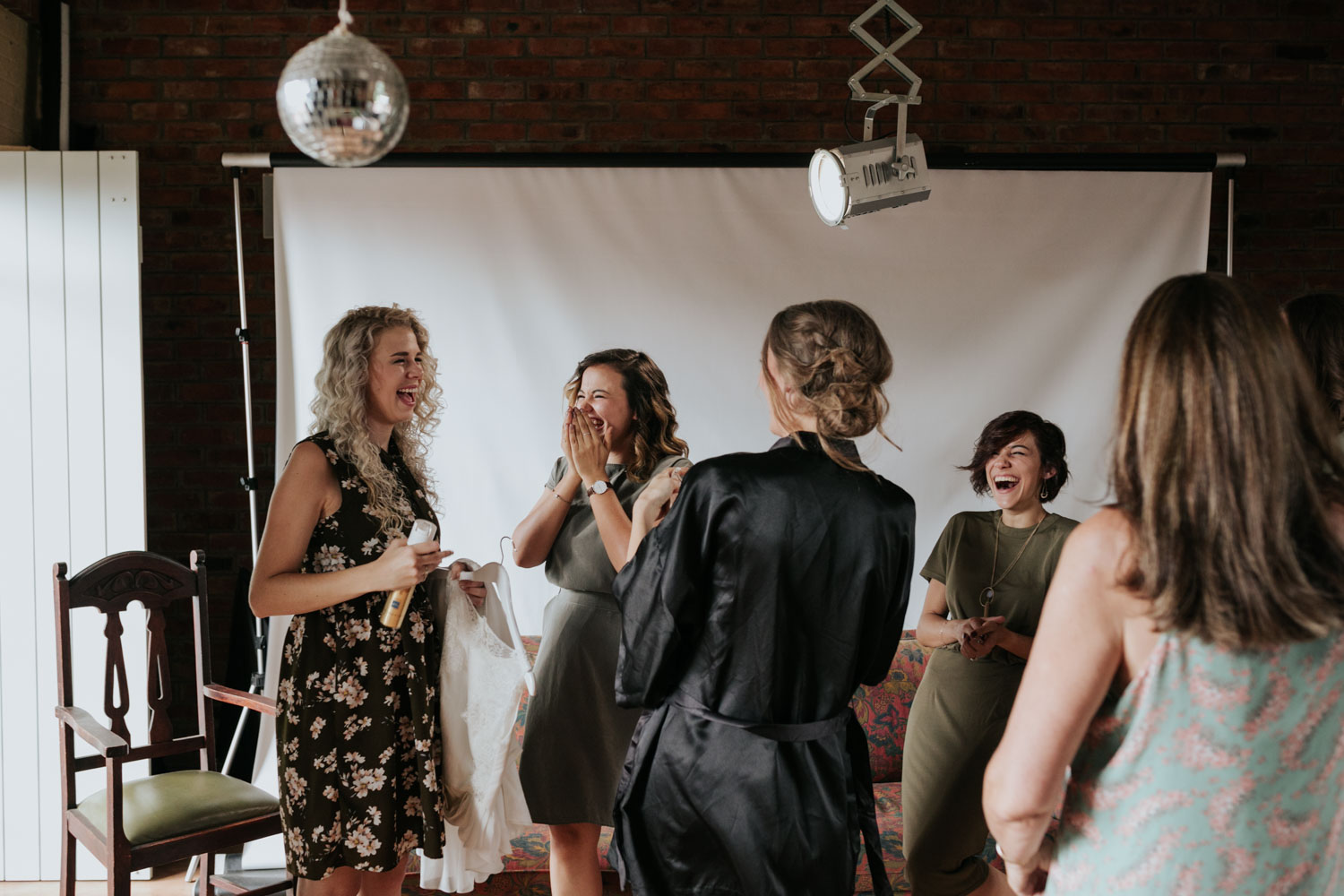 Candid Happy Moment Of Bride Wearing Black Silk Gown Laughing With Bridesmaids