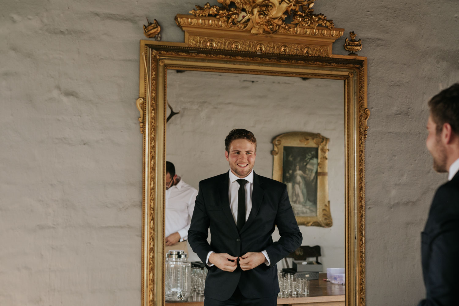 Groom Reflection In Mirror As He Puts On Black Suit At Interesting Vancouver Boutique Hotel