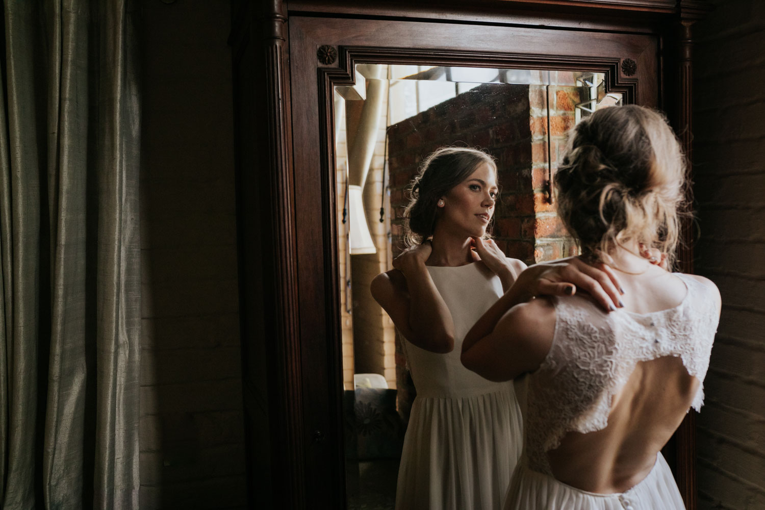 Bridal Portrait Wearing Lace Dress With Circle Cut Out In Back Looks In Antique Mirror