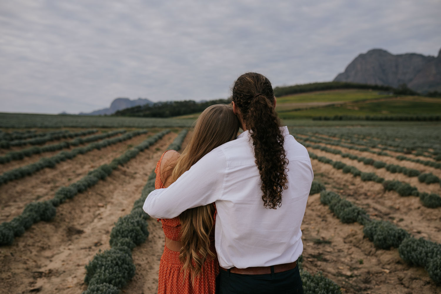 Boho Long Haired Couple Stand In Farm Field At Babylonstoren In Mountains Near Cape Town