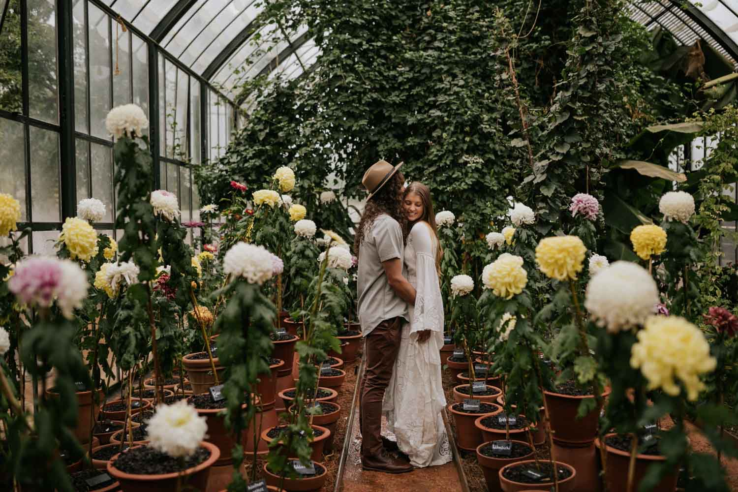 Greenhouse Engagement Photo Shoot With Boho Long Haired Couple