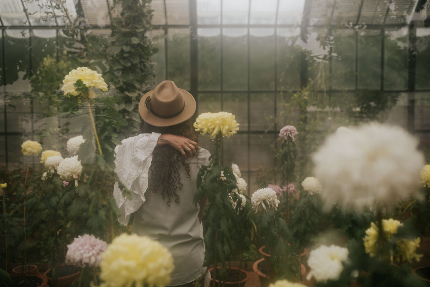 Greenhouse Engagement Photo Shoot With Boho Long Haired Couple In Flowers