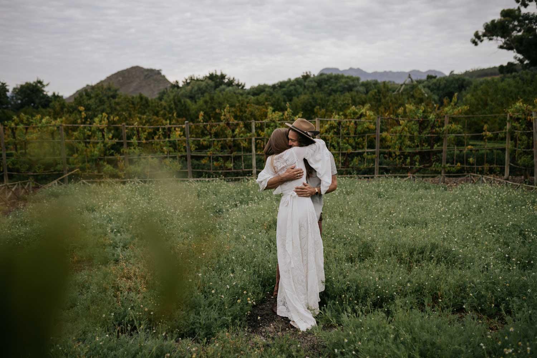 Boho Bride And Groom Hug in Camomile Field at Babylonstoren Cape Town Wedding Venue