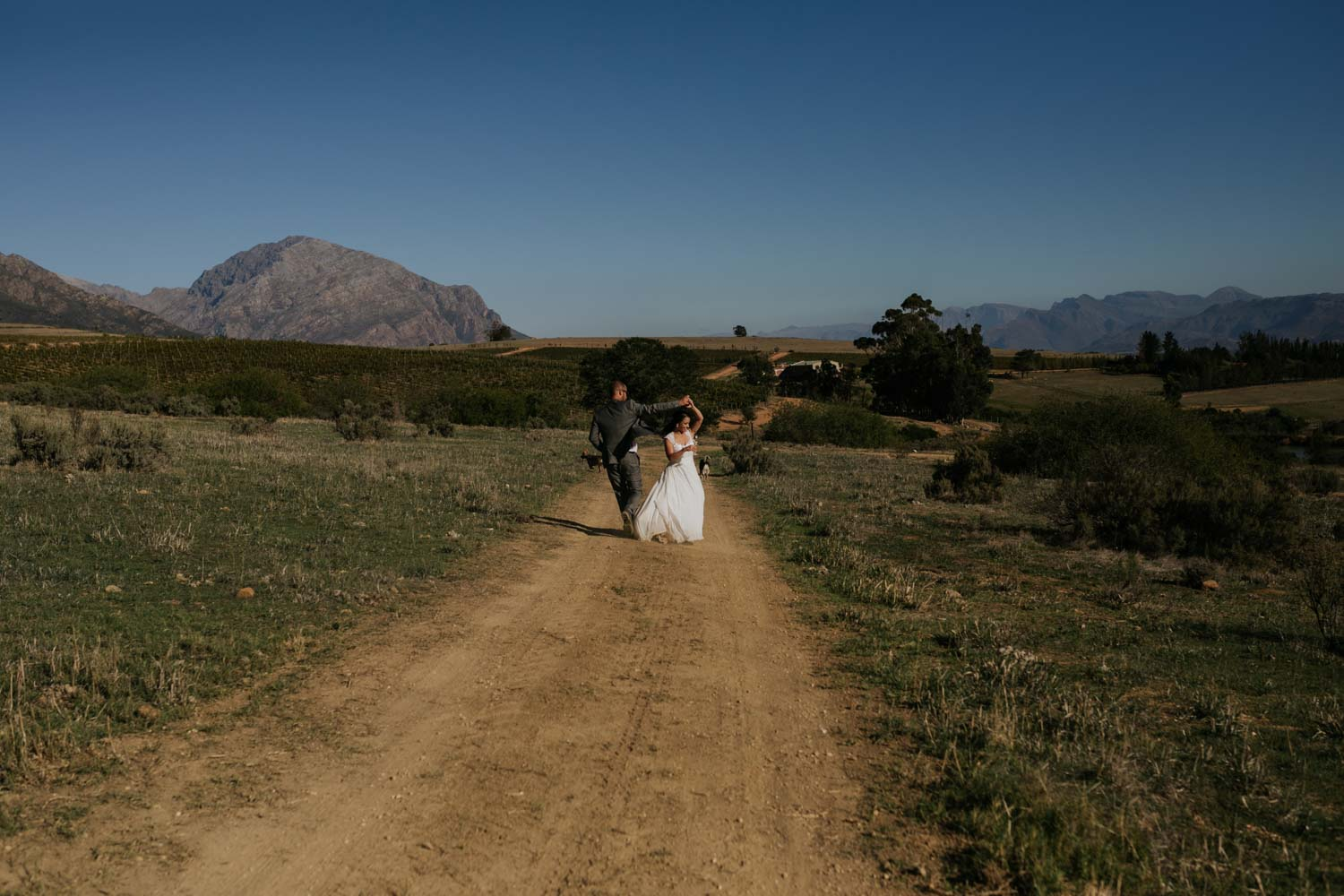 Bride and groom dancing on a dusty farm road near Cape Town, South Africa.