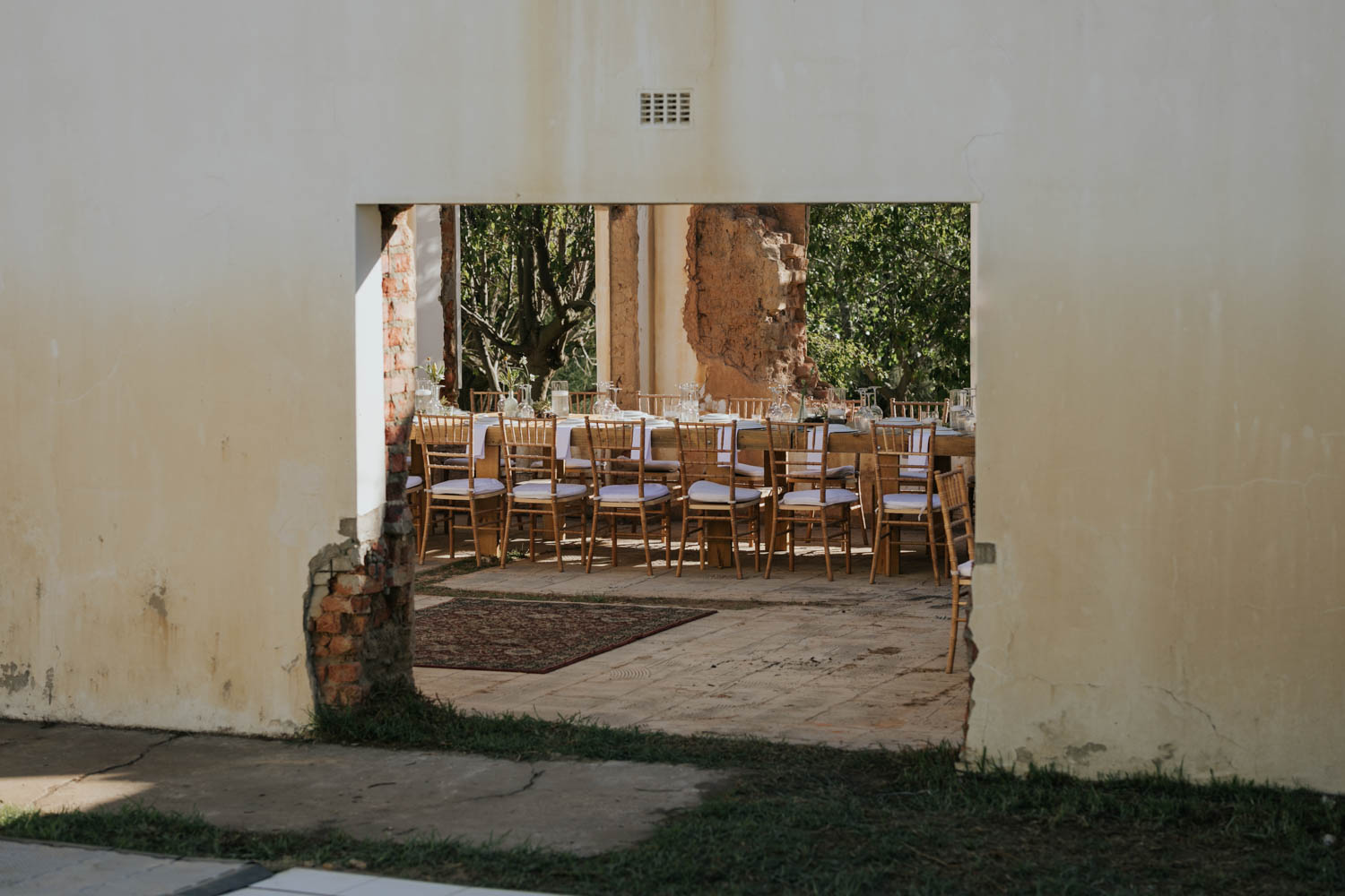Simple wedding decor, wooden chairs and white linen table cloths setup in the ruins of an old farm house.