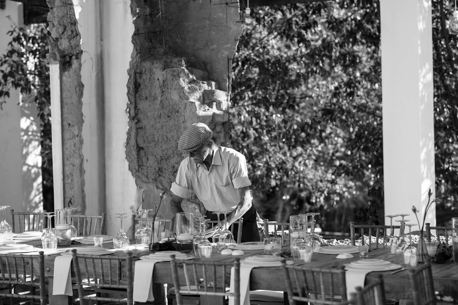 Old man with hat setting up the table for a lazy wedding lunch in Tulbagh, Cape Town.