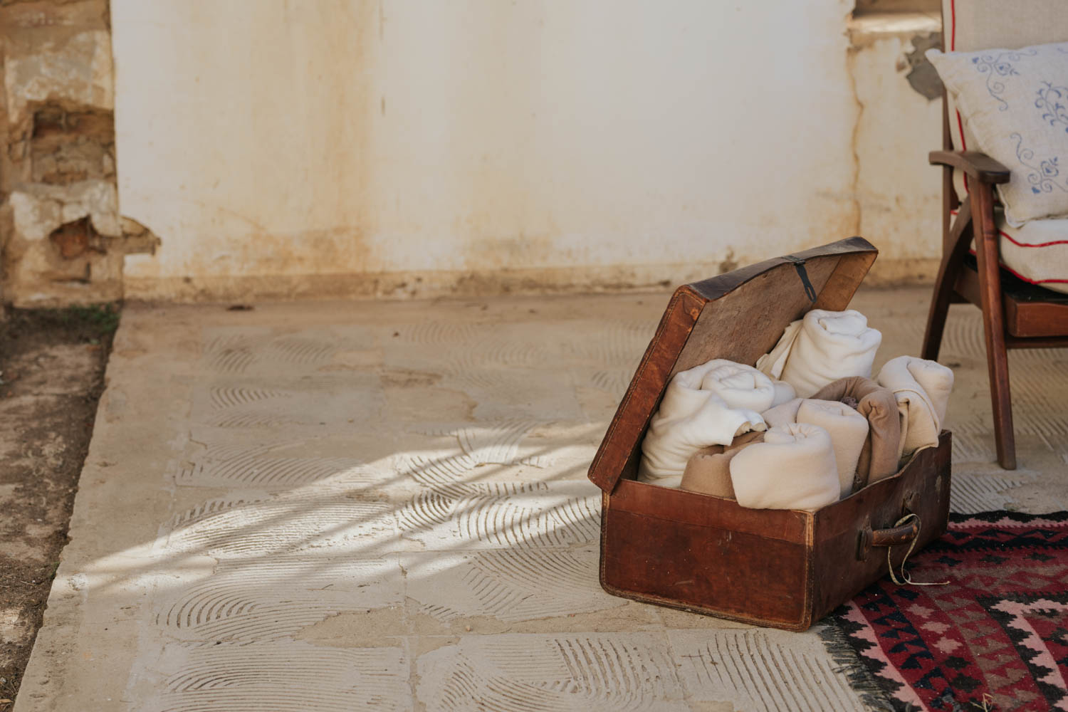 Old leather suitcase with filled with blankets to keep wedding guests warm during wedding ceremony