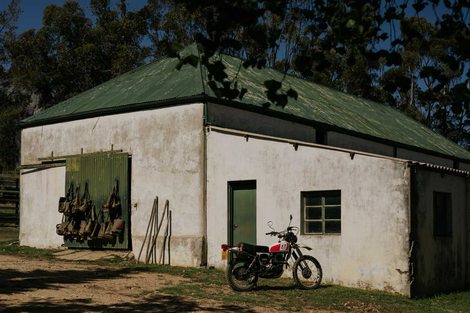 An old white farm shed with green doors and roof with motor bike outside