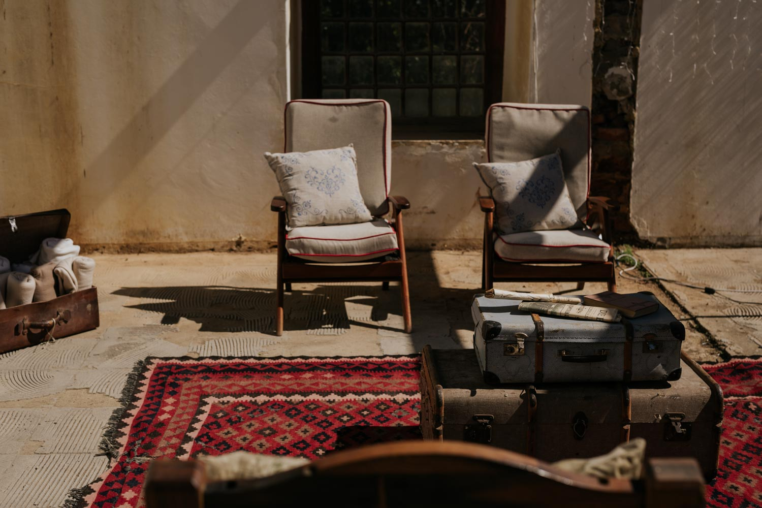 Two old midcentury chairs setup on an Persian rug for wedding guests to sit on during cocktail hour