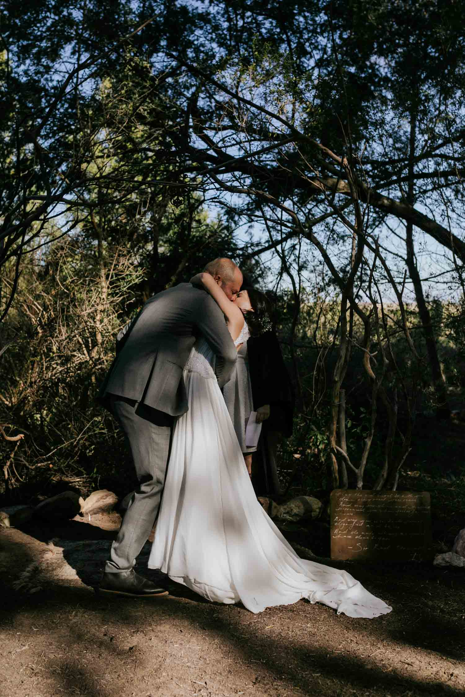 Bride and groom's first kiss in forest on a farm in Tulbagh, Cape Town.