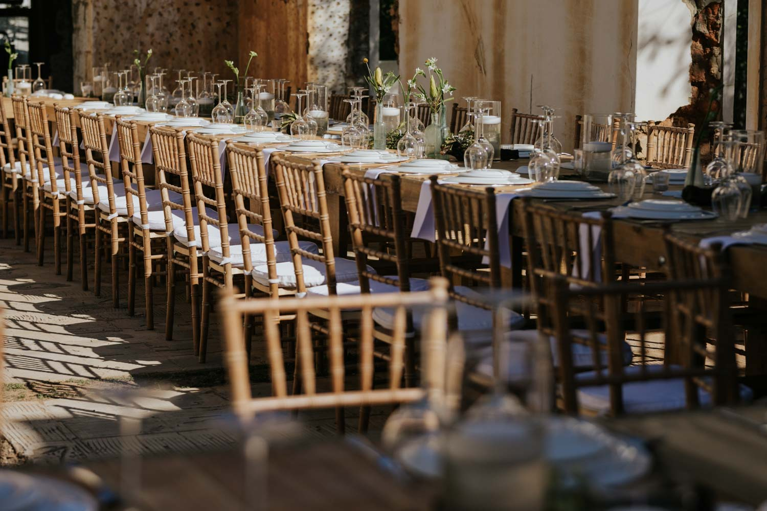 Long wooden wedding tables set with simple green flower arrangements, white linen, candles and glass.