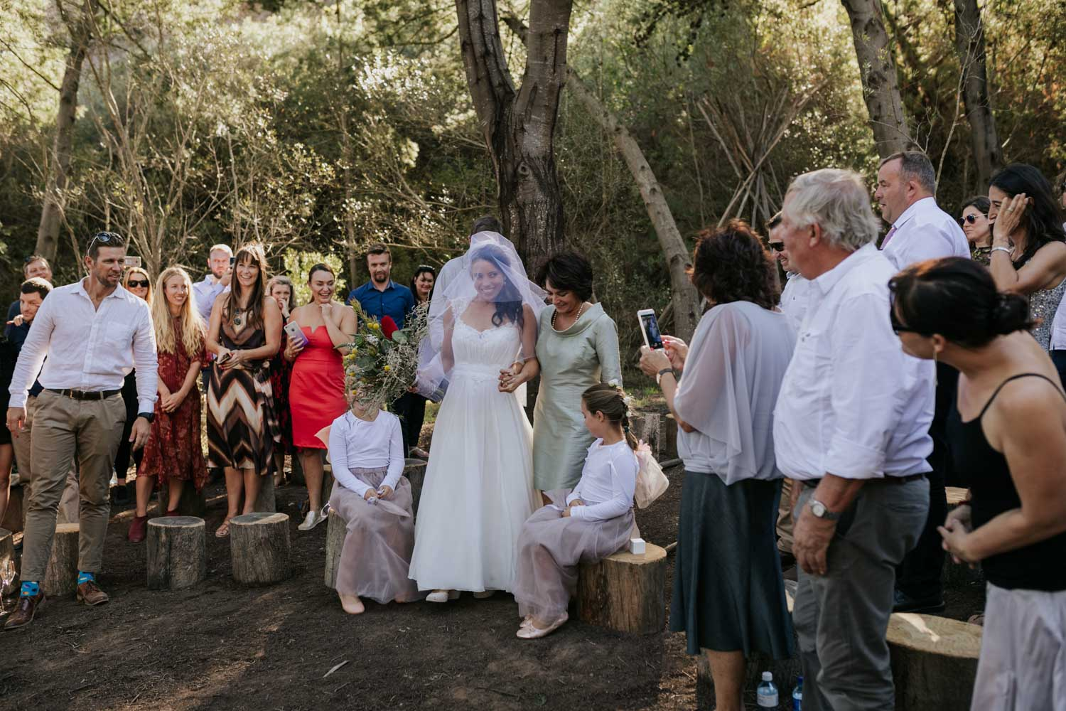 Bride's mother walks her down the aisle in a forest with guests sitting on tree stumps towards her soon to be husband.