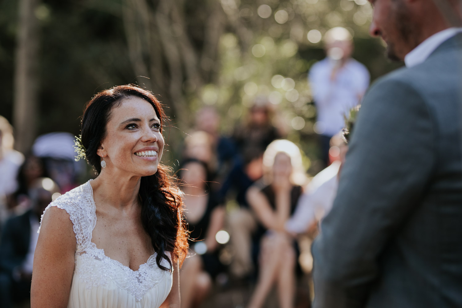 Natural bride with curly brown hair and a simple lace dress looking up adoringly at her husband during their farm wedding ceremony in a forest close to Cape Town.