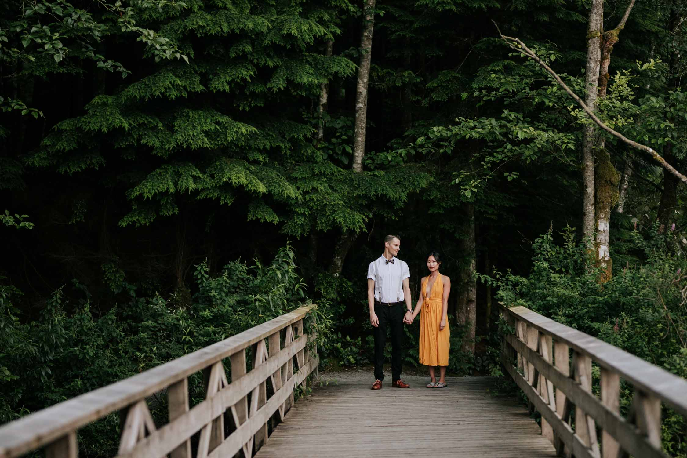 Mixed couple stand on wooden bridge at Rice Lake holding hands. She is Chinese and is wearing a yellow dress, he is white and is wearing a bowtie.