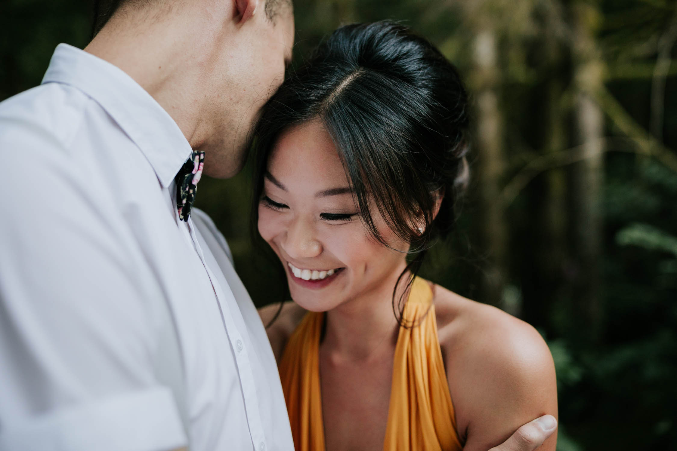 Chinese girl wearing a yellow dress laughs as her finance whispers in her ear.