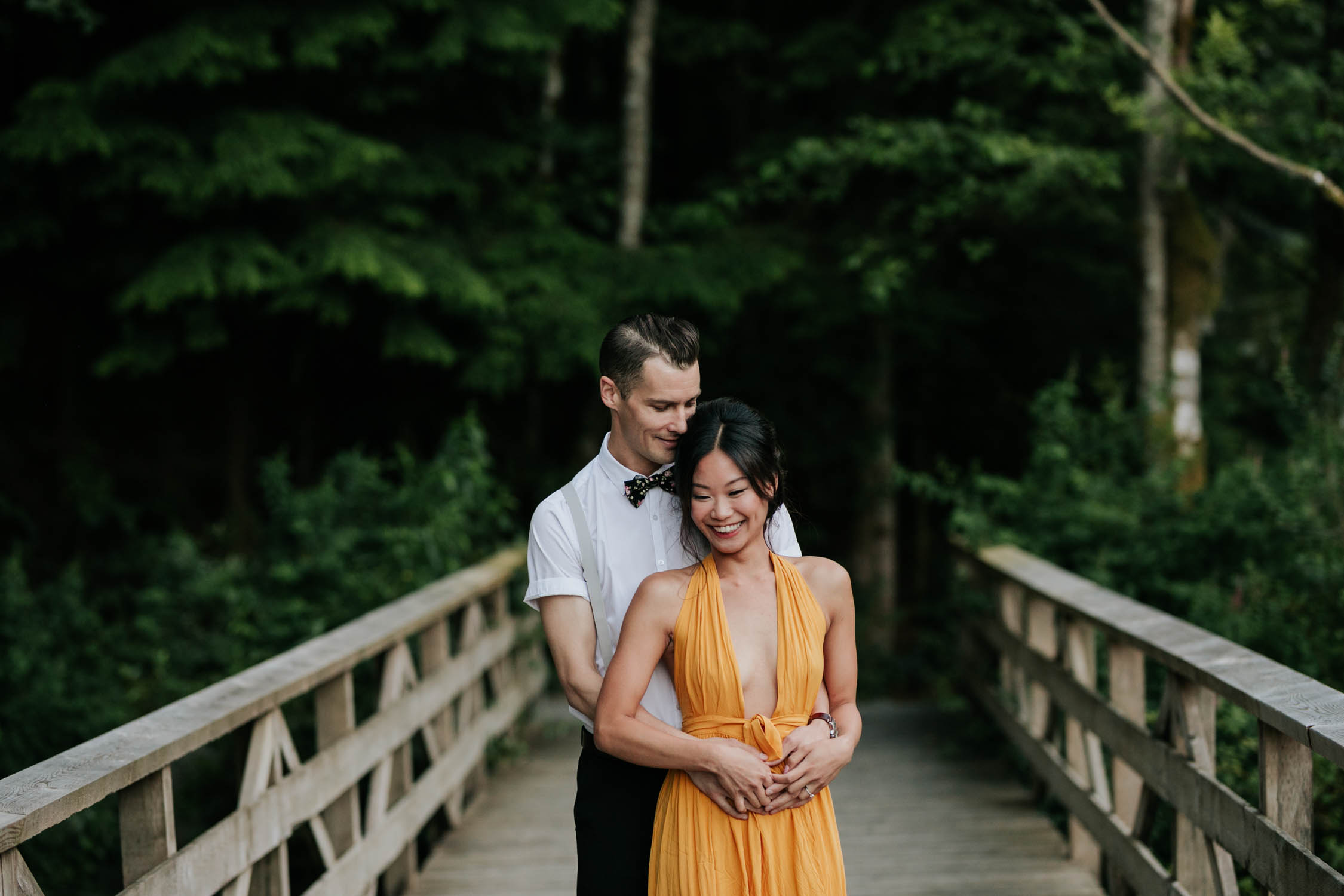 Natural moment captured of engaged couple laughing together on a bridge.
