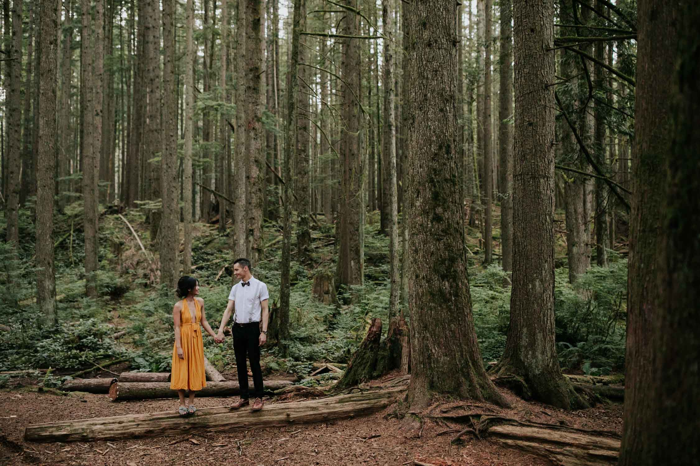 Couple stand on a log surrounded by forest in Vancouver, BC.