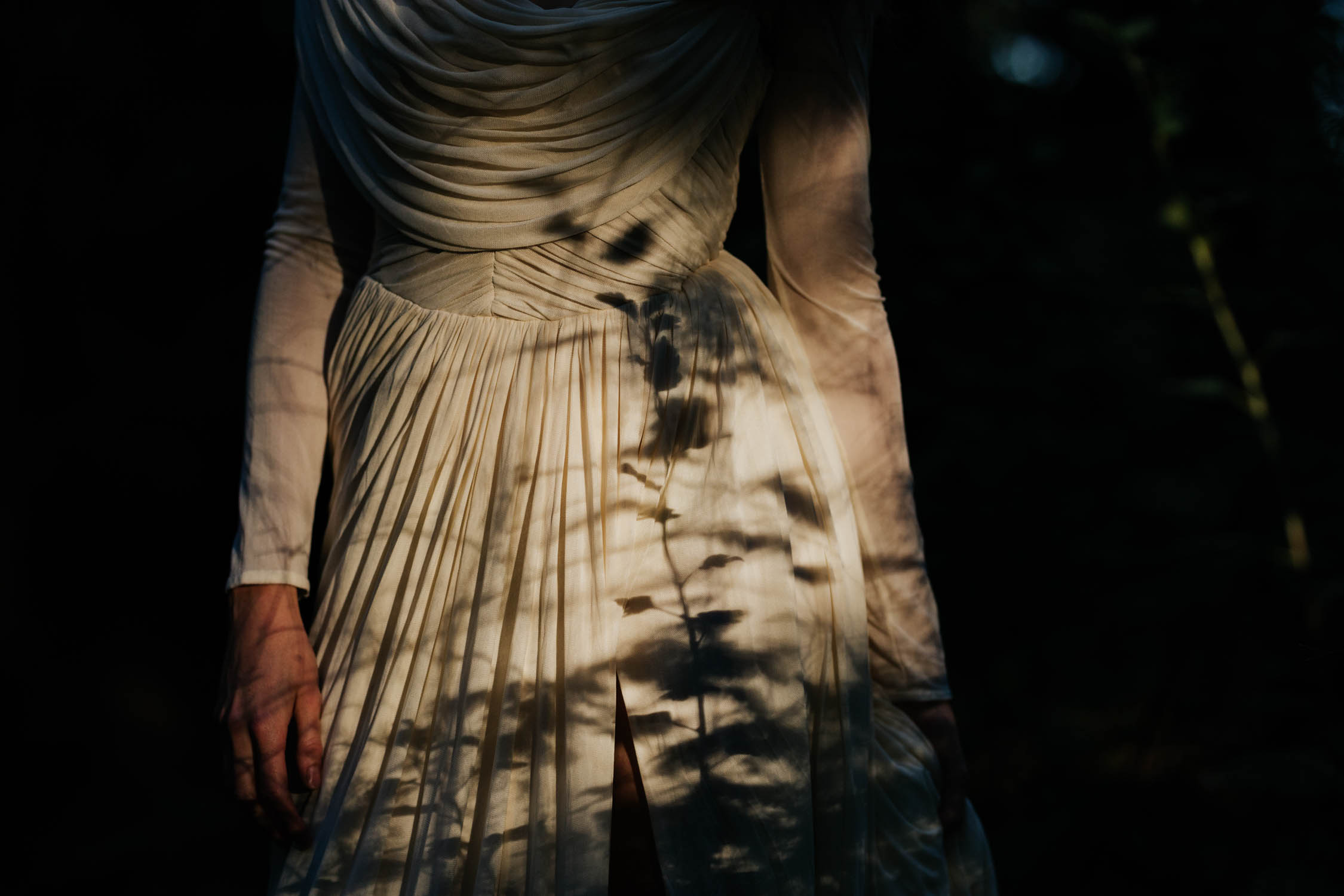 Bride standing in forest with the shadows from the forest flowers and leaves reflecting on her elegant silk wedding dress. Shadow looks like a rose.
