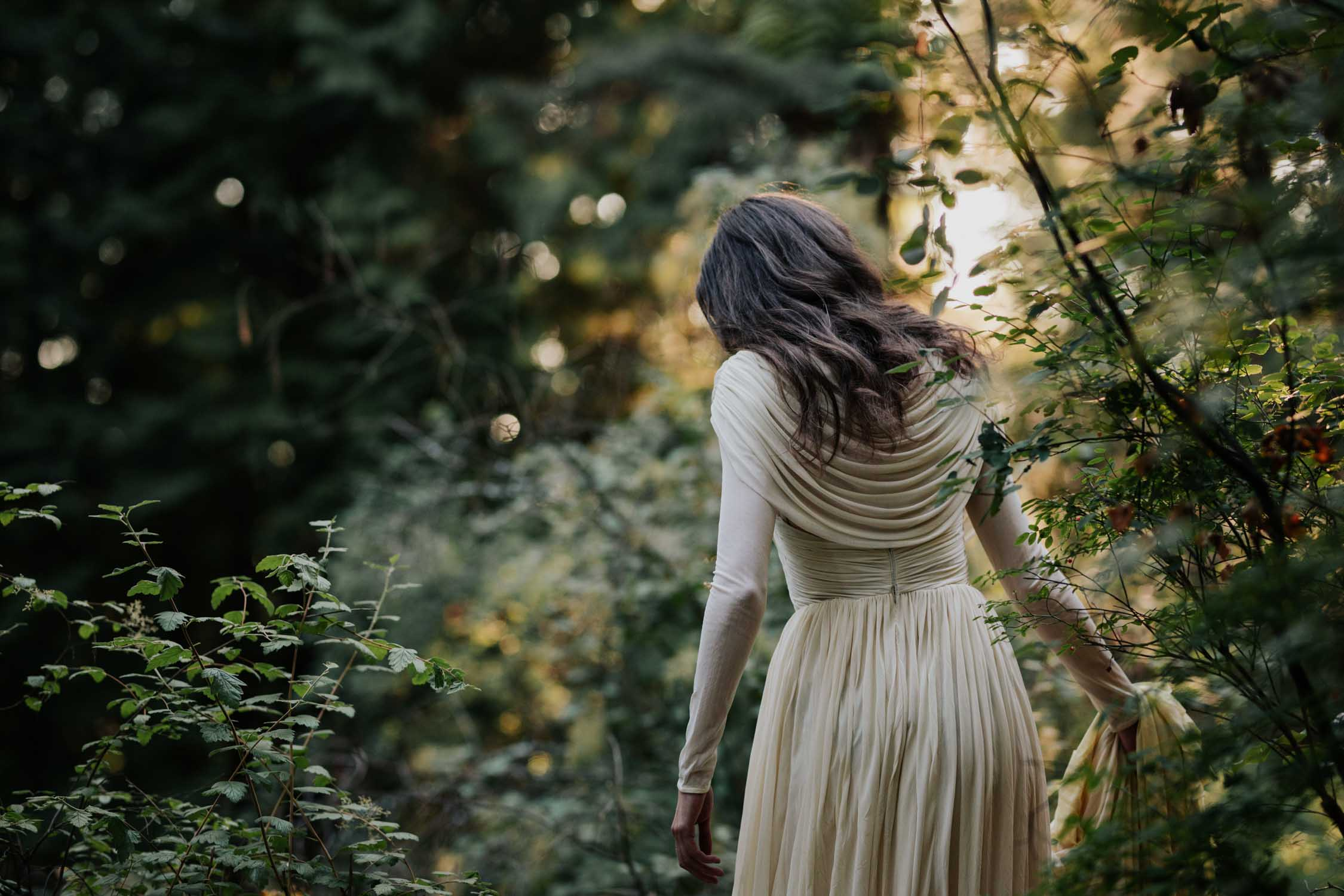 Candid Moment Of Bride Walking Through Forest Light and Trees