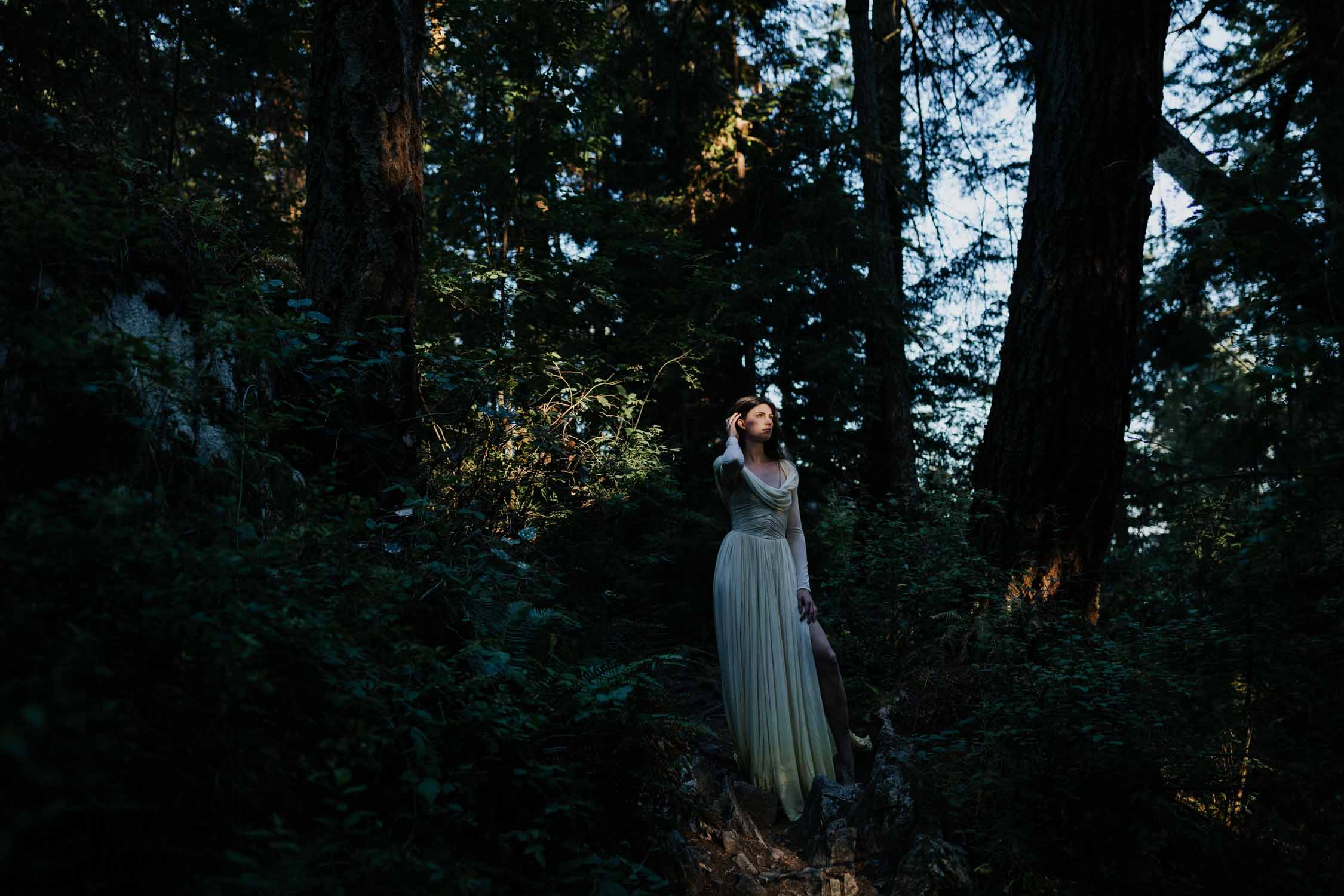 Light shining on the face of a bride, like a spotlight, as she stands in a dark forest in Lighthouse Park. Alternative Vancouver Wedding Photographer.