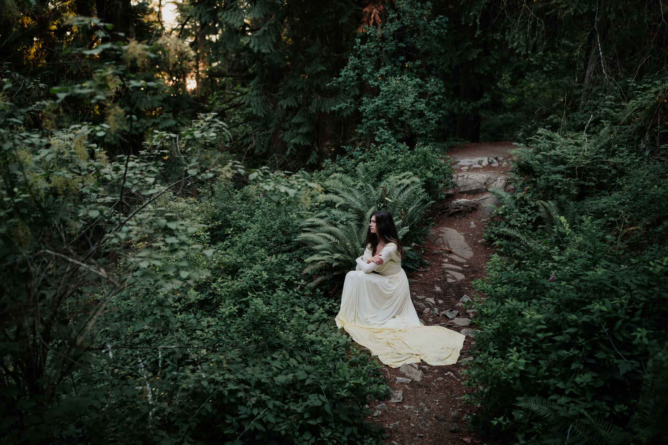Bride sitting in a forest of lush green ferns at Light House Park in Vancouver with the light shining behind her through the forest. Alternative and natural wedding photographer.