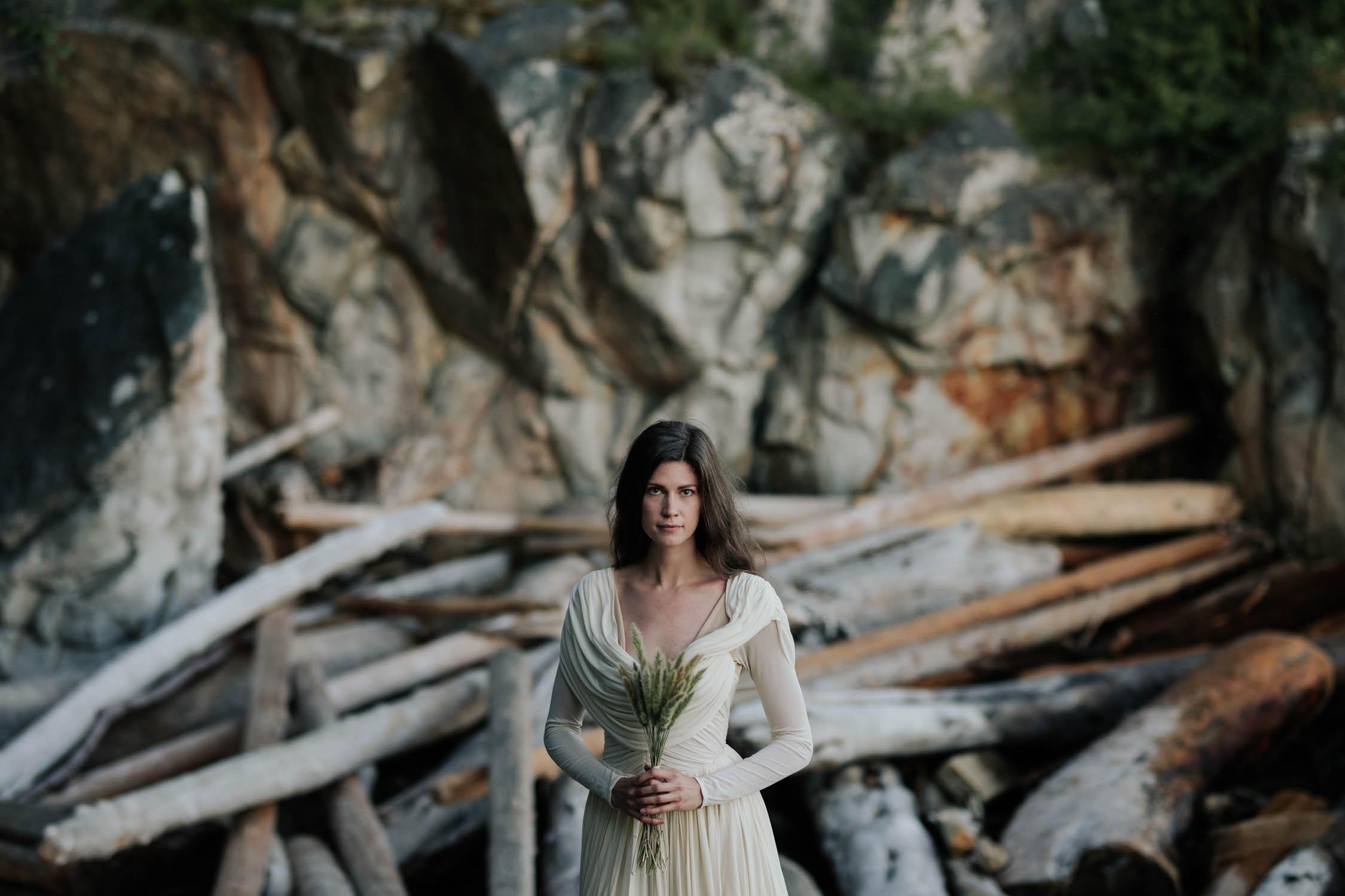 Bride Wearing Long Sleeved Silk Wedding Dress Holds Unusual Natural Grass Bouquet