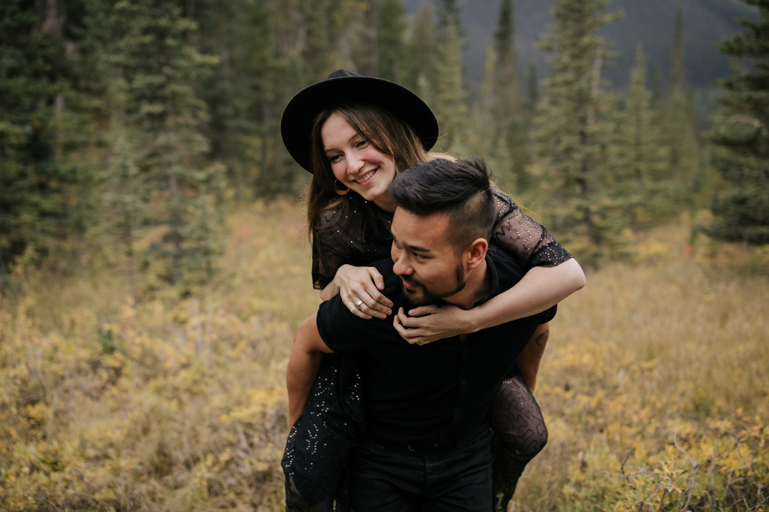 Fun Happy Groom Gives Boho Bride Piggyback In Canmore Field Alberta Wedding